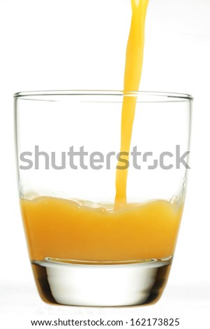 Orange juice being poured into clear glass tumbler. - stock photo