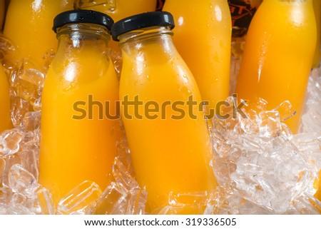 Orange juice bottles on the ice box - stock photo