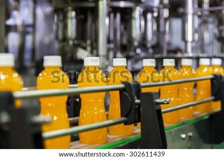 Orange Juice Bottles transfer on Conveyor Belt System - stock photo
