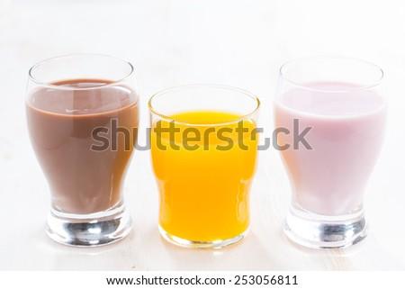orange juice, chocolate milk and fruit yoghurt on white table, close-up - stock photo