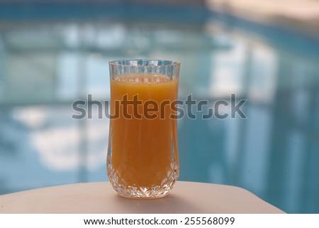 orange juice glass in front of pool - stock photo