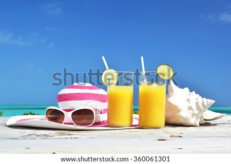 Orange juice, hat, sunglasses and conch on the tropical beach. Exuma, Bahamas - stock photo