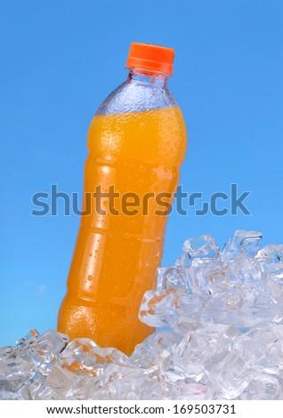 Orange juice In a bottle on the ice background. - stock photo