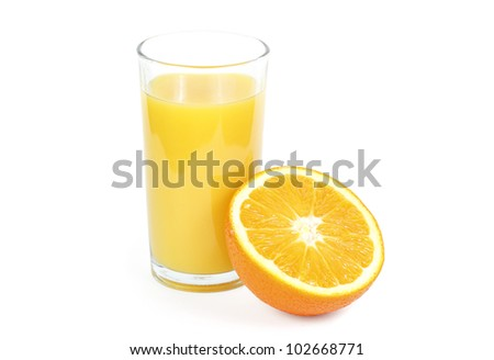 Orange juice in a glass and cut oranges