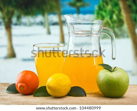orange juice in a glass on a table with oranges - stock photo
