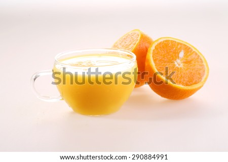 Orange juice in a transparent cup and halves of a juicy ripe orange on a white background  - stock photo