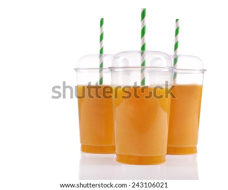 Orange juice in fast food closed cups with tubes isolated on white - stock photo