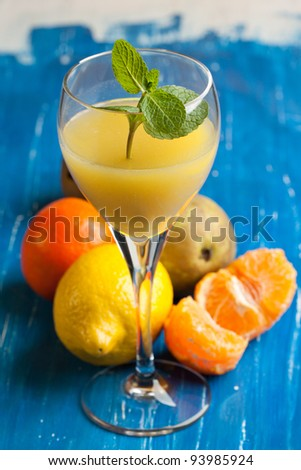 Orange juice in glass and fresh exotic fruits on blue and white wooden table