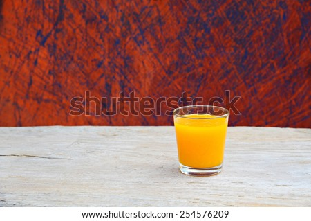 orange juice in glass on wooden background - stock photo
