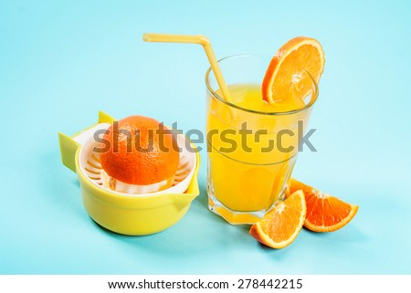 Orange juice in glass with orange slices and orange strainer/Orange juice in glass
