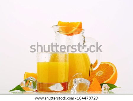 orange juice in the glass and pitcher with pieces or fresh oranges and ice cubes - stock photo