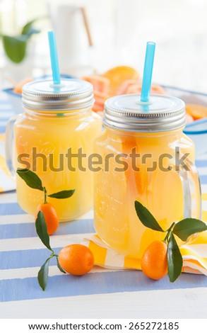 Orange juice in vintage jars with fresh kumquats - stock photo