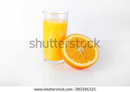 Orange juice is poured into a glass Orange in a cut