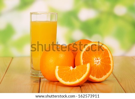 Orange juice on a wooden table against green foliage