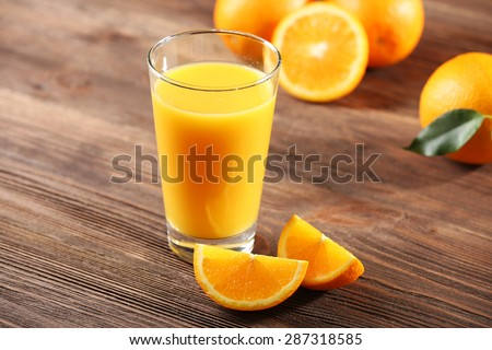 Orange juice on table on wooden background - stock photo