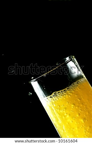 orange juice poured in a glass on black background