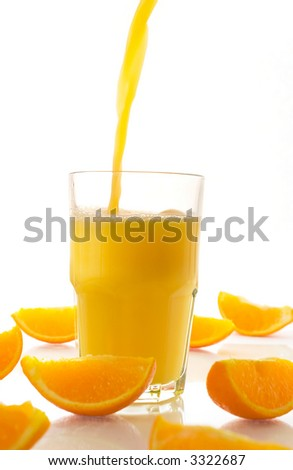 Orange juice pouring into a glass surrounded by orange slices, white background.