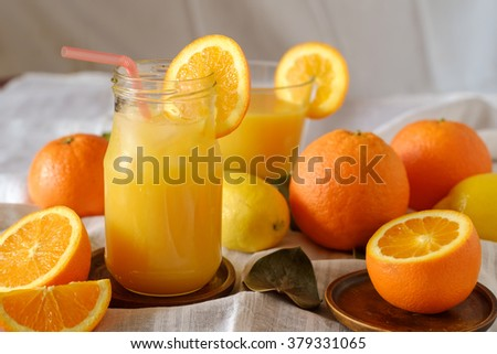Orange juice with ice on table with oranges and lemons - stock photo