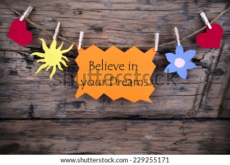 Orange Lable Saying Believe In Your Dreams On Wooden Background Hanging On A Line, Two Red Heart Symbols And One Yellow Sun Symbol And One Blue Flower Symbol,Background Is Old Fashion - stock photo