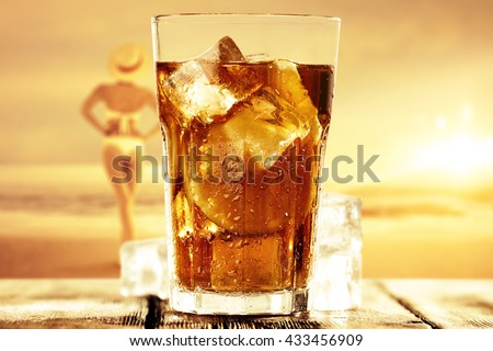 orange landscape of sea and summer time on beach with glass of ice tea  - stock photo