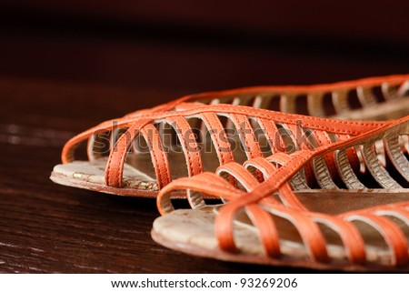 Orange leather ladies sandals on wooden background - stock photo