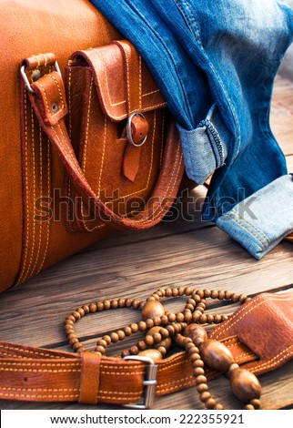 orange leather vintage suitcase travel bag, old fashioned beads and jeans on a wooden floor - stock photo