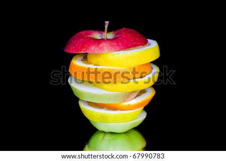 Orange lemon and apple slices composition isolated on black background - stock photo