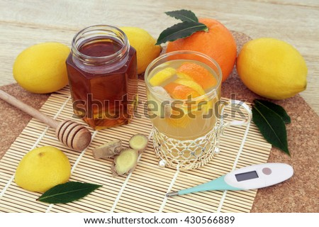 Orange, lemon and honey drink with ginger spice and fresh fruit and thermometer on bamboo and cork background. - stock photo