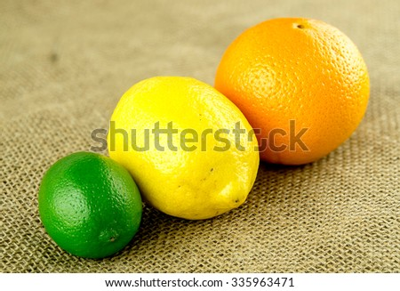 Orange, lemon and lime on hessian backdrop - stock photo