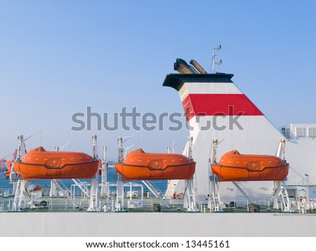 Orange life boats on a cruiseship docked at port waiting for passengers to board - stock photo
