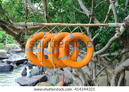 orange life buoy within the waterfall area. - stock photo