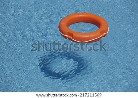 Orange life rings in blue water. Horizontal format - stock photo