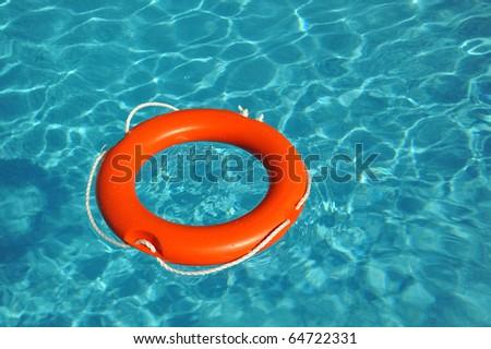 Orange lifebelt floating in blue water - stock photo