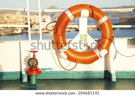 Orange lifebelt on a deck - stock photo