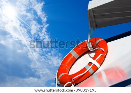 Orange Lifebuoy on a Ferry Boat / Detail of an orange lifebuoy on a white passenger ship with blue sky, clouds and sun rays - stock photo