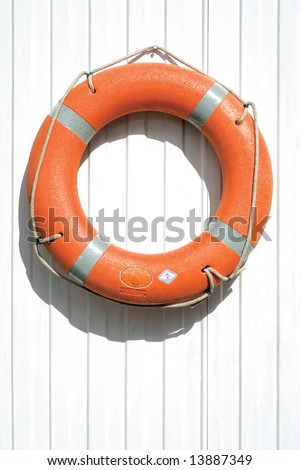 Orange lifebuoy on fence. A view of an orange lifebuoy or rescue device on a white fence. - stock photo