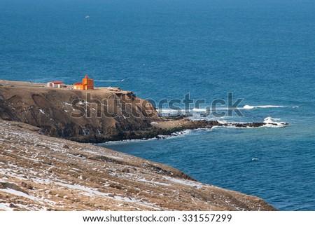 Orange lighthouse at the north coast of Iceland - stock photo