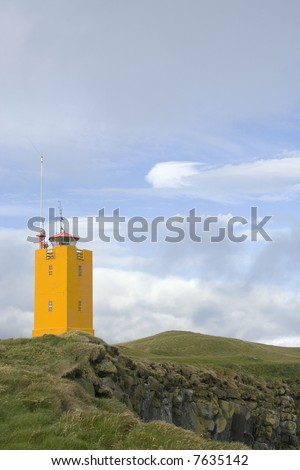 Orange lighthouse on Icelandic cliff - stock photo