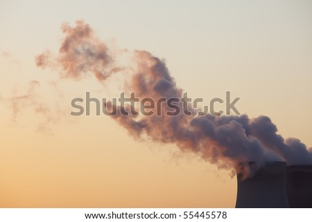Orange lit by the late evening sun, smoke is coming out of the nuclear power plant in Doel, Belgium, in the harbor of Antwerp - stock photo