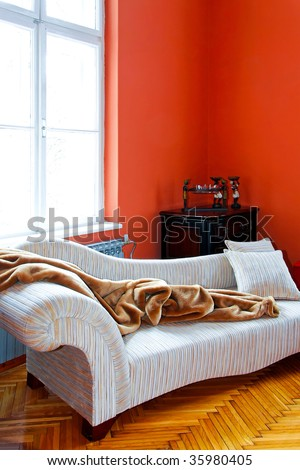 Orange living room corner with retro sofa - stock photo