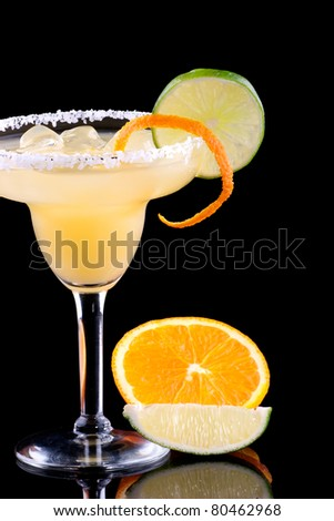 Orange Margarita in chilled glass over black background on reflection surface, garnished with fresh lime and orange. Most popular cocktails series. - stock photo