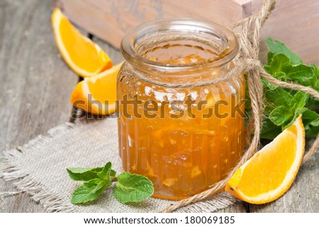 orange marmalade in a glass jar, close-up, horizontal - stock photo