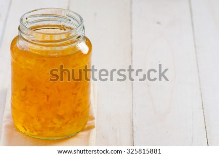 Orange marmalade jam in glass on wood background