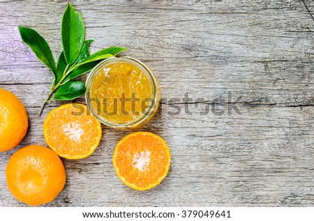 Orange marmalade on wooden table with fresh fruit  - stock photo