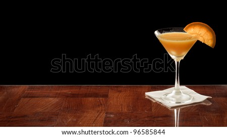 orange martini on a bar top garnished with an orange slice over black - stock photo