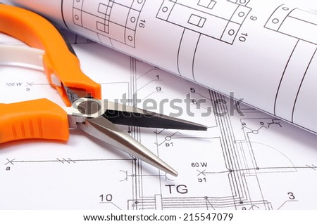 Orange metal pliers with rolled electrical diagram lying on construction drawing of house, work tool and drawings for the projects engineer jobs