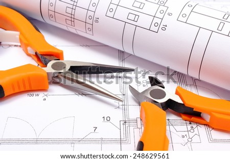 Orange metal pliers with rolled electrical diagram lying on construction drawing of house, work tool and drawings for the projects engineer jobs - stock photo