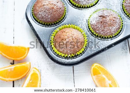 Orange muffins in baking dish and sliced orange - stock photo