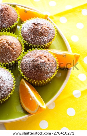 Orange muffins on the big green plate and sli?ed orange - stock photo