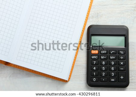 orange notebook on a white wooden background with a calculator